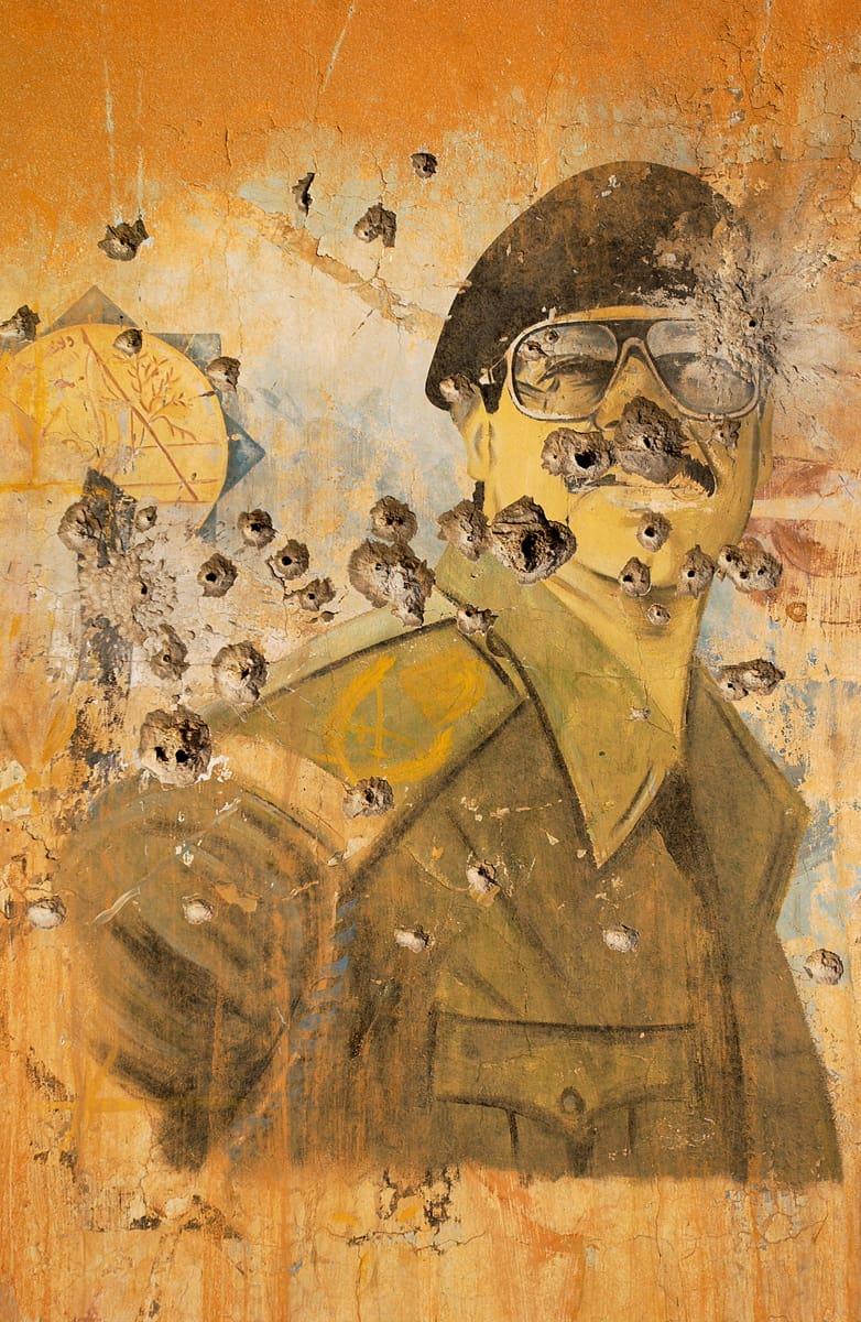 Portrait mural de Saddam Hussein perforé de balles par les forces américaines, Irak, avril 2003 ©James Hill