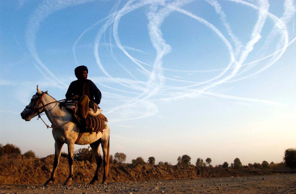 Un homme regarde les avions américains dans le ciel de Kalakata, Ville de Deshtikala Afghanistan, novembre 2001 JH003 ©James Hill