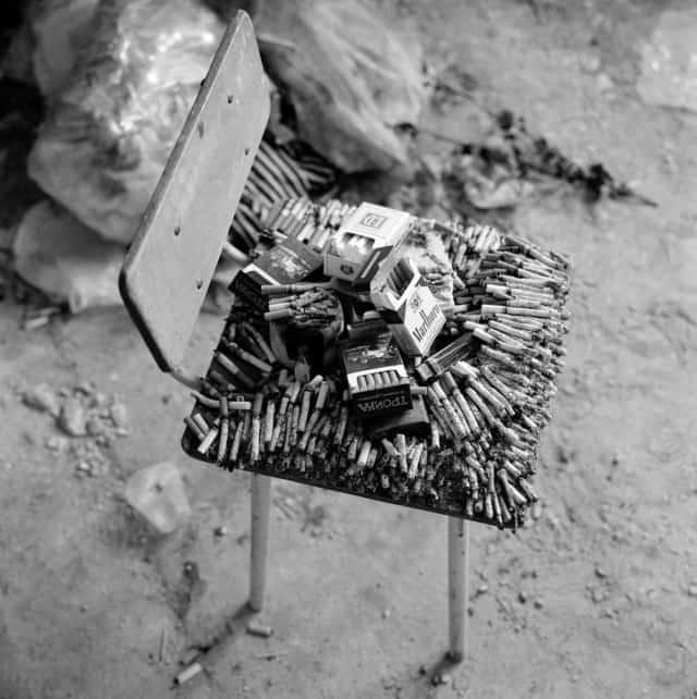Cigarettes brûlant sur une chaise en signe de respect pour les hommes exécutés dans cette salle de classe de l'école de Beslan, Russie, 2004 ©James Hill